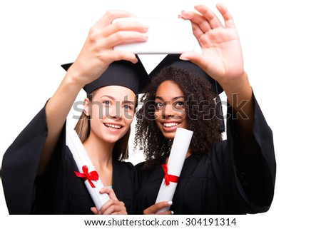 Self ie fun. Two young student girls dressed in black graduation gown. Isolated on white background. Girls smiling, making photo of themselves on phone and holding diplomas