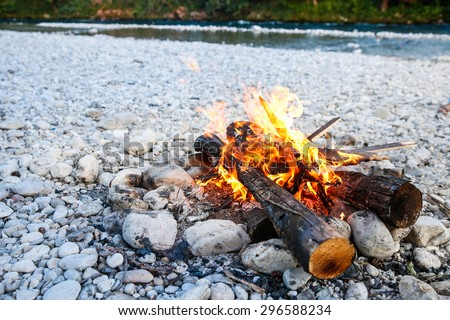 Self-made campfire by the mountain river, lit for cooking, roasting and water purification. Safety and survival, fun family activity concept.  - stock photo