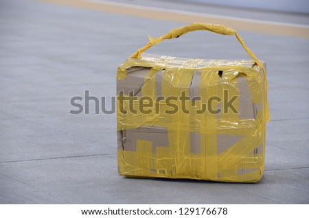 Self made carton suitcase laying on railway station floor. Looking suspect. - stock photo