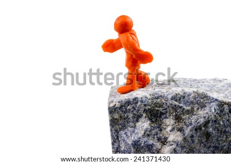 Self-made human plasticine figure walking to the edge of the abyss. - stock photo