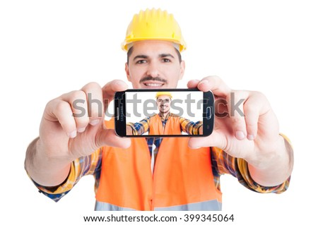 Self-portrait concept with handsome young engineer in protection workwear holding a smartphone isolated on white background - stock photo