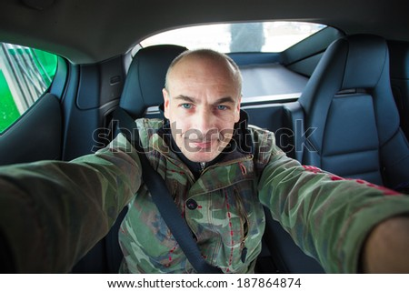 self-portrait in the car of an adult male. man in uniform behind the wheel of a car. Clothing color khaki - stock photo