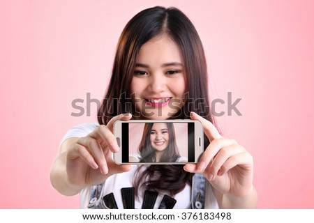 Self shot picture on smartphone screen of cute Asian girl, over pink background - stock photo