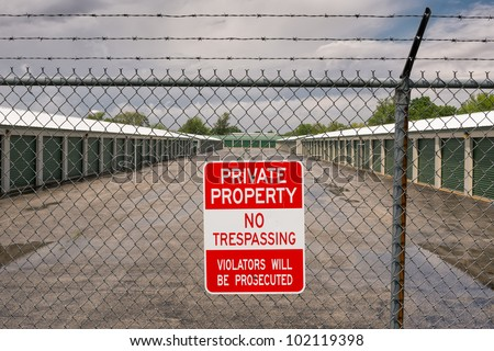 Self storage facility with no trespassing sign on barbed wired fence - stock photo