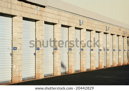 Self storage warehouse metal roll up doors closed in a row.