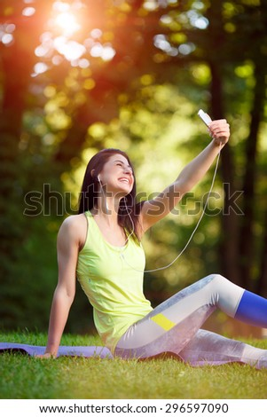 Selfie, Cheerful fitness woman taken pictures of her self phone, instagram. Beautiful brunette in sportswear photographs himself in a park in the sunshine - stock photo