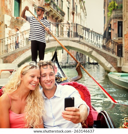 Selfie couple in gondola on Venice travel vacation. Beautiful lovers on a romantic boat ride across the Venetian canals taking self-portrait pictures with smartphone app during their summer holidays.