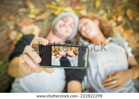 Selfie - Couple taking a self portrait while lying on meadow with yellow leaves - stock photo
