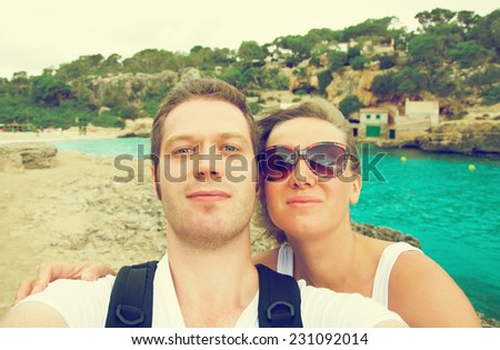 Selfie. Couple taking picture on the beach. Vintage effect photo. - stock photo