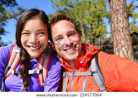 Selfie couple taking self-portrait hiking using smart phone camera in nature. Happy couple taking self-portrait photo picture looking at camera smiling happy. Man and woman having fun together. - stock photo
