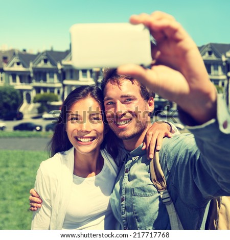 Selfie - Couple taking self-portrait photo in San Francisco with smartphone camera. Happy tourist couple on travel vacation in San Francisco, Alamo Square, USA. Heavily filtered Instagram style. - stock photo