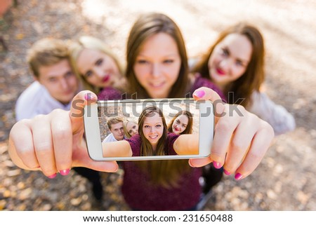Selfie for social network with photobomb with a group of young people. - stock photo