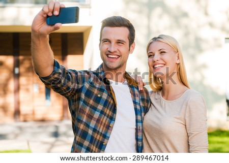 Selfie for their family album. Cheerful young couple bonding to each other while making selfie by smart phone while standing against their new house  - stock photo