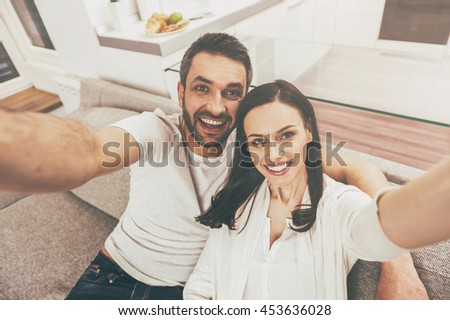 Selfie fun. Top view of happy loving couple bonding to each other and making selfie while sitting on the couch together - stock photo