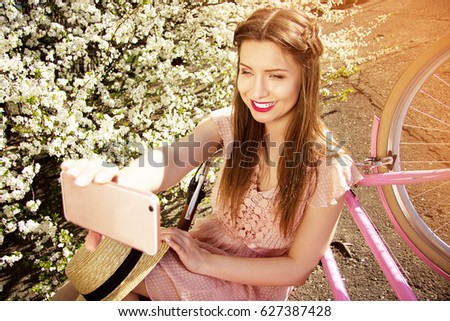 Selfie girl. Portrait of smiling young and beautiful long-haired girl in pink dress taking selfie on her phone on flower background.