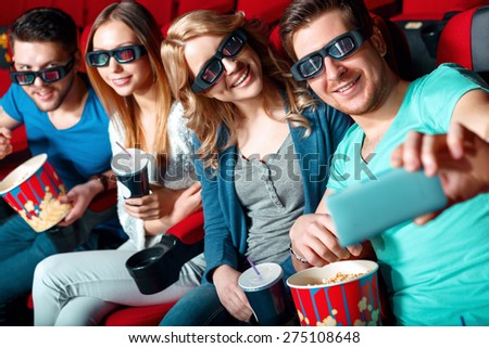 Selfie. Group of cinema visitors in glasses doing selfie with popcorn and coke. - stock photo