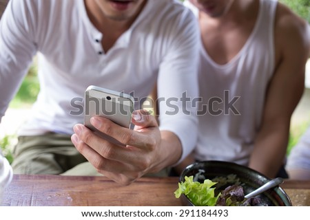 man using app a smartphone playing social network Happy gay couple
