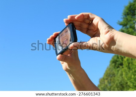 selfie - happy girl takes a self portrait with her mobile phone under blue sky and green trees  background