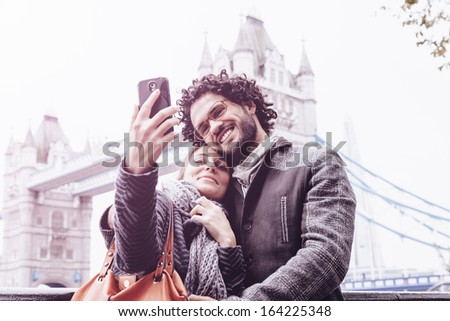 Selfie - Loving couple taking pictures with your cell phone in front of Tower Bridge, London - stock photo