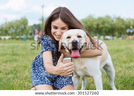 Selfie of a woman with her beautiful dog lying outdoors. Training the dog - stock photo