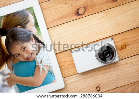 Selfie of asian daughter and mother on the screen of tablet computer with digital camera on wooden table - stock photo