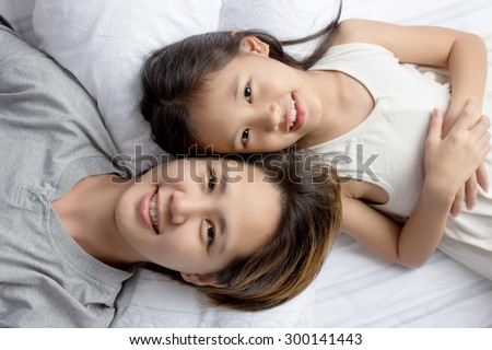 Selfie of happy Asian mother lying  with daughter on the bed