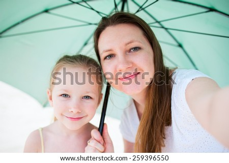 Selfie of happy mother and her adorable little daughter outdoors with umbrella on rainy summer day - stock photo