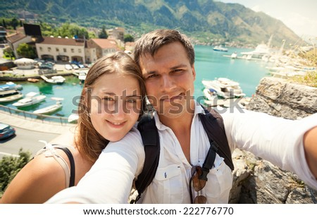 Selfie of young happy couple posing against sea bay at sunny day - stock photo