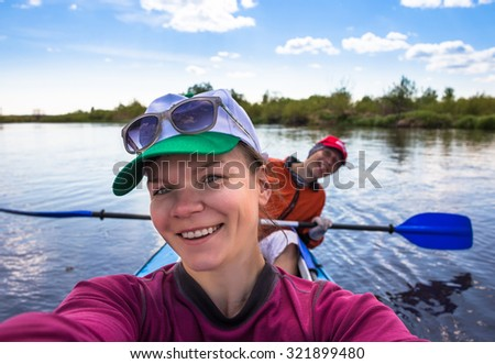 Selfie on kayak. Young people are kayaking on a river in beautiful nature. Summer sunny day in outdoor - stock photo