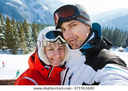Selfie or young couple in winter ski resort