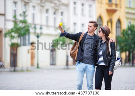 Selfie photo by caucasian couple traveling in Europe. Romantic travel woman and man in love smiling happy taking self portrait outdoor during vacation holidays in Prague - stock photo