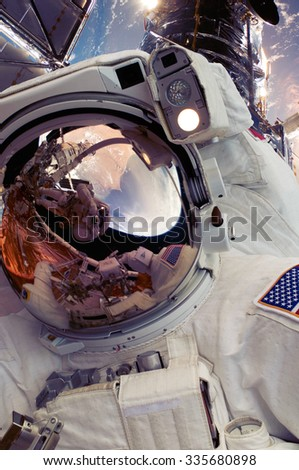 Selfie photo of astronaut spaceman in outer space with people on planet earth moonon on space mission. Warm color filter. Elements of this image furnished by NASA. - stock photo