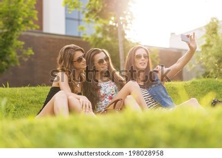 Selfie Photo.3 pretty woman enjoying the nice weather on the grass.  - stock photo