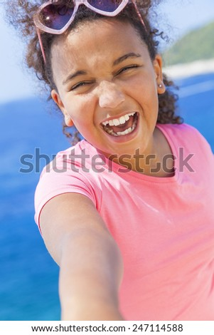 Selfie photograph of laughing happy mixed race African American female girl child wearing sunglasses in bright sunshine on vacation in front of a blue tropical sea - stock photo