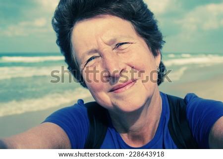 Selfie portait of happy senior woman on the beach - stock photo