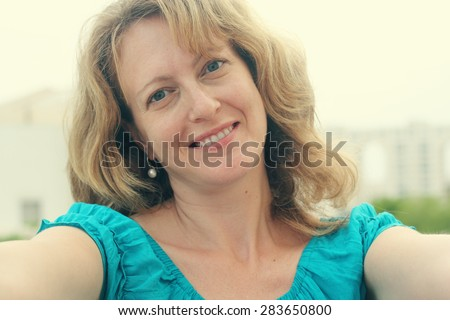 selfie portrait of beautiful 35 years old woman. Instagram filter. - stock photo