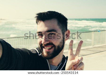 selfie portrait of young man outdoors - stock photo