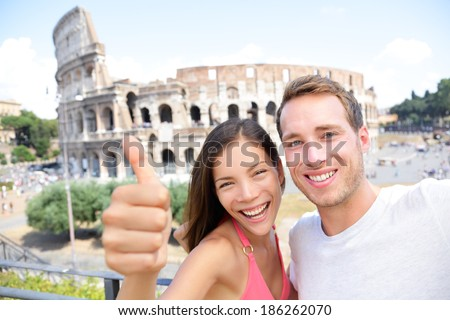 Selfie - Romantic travel couple by Coliseum, Rome, Italy. Happy lovers on honeymoon sightseeing having fun in front of Colosseum. Woman giving thumbs up in tourism travel concept. - stock photo