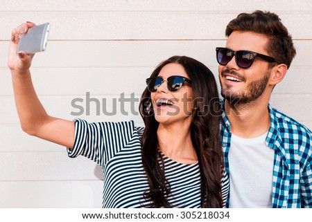 Selfie time. Beautiful young loving couple making selfie on smart phone while standing outdoors - stock photo