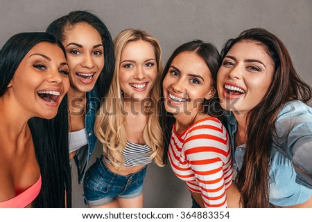 Selfie time! Five beautiful women bonding to each other and smiling while making selfie against grey background - stock photo