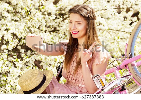 Selfie time. Portrait of smiling beautiful and young long-haired girl in pink dress taking selfie on her phone. Flower background.