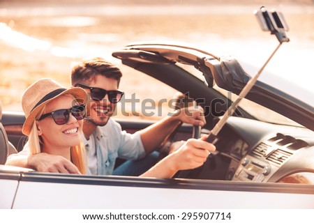 Selfie to remember the day. Happy young couple using monopod while making selfie inside of their convertible - stock photo