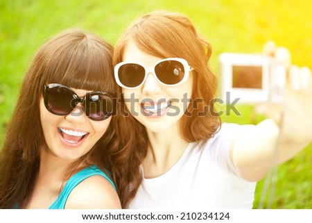 Selfie. Two young trendy girls doing selfie. A couple of friends photographing themselves. Two women did a photo shoot in nature. - stock photo