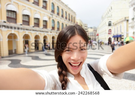 Selfie woman taking fun selfportrait in Macau, China in Senado Square or Senate Square. Asian girl tourist using smart phone camera to take photo while traveling in Macau. Travel and tourism concept. - stock photo