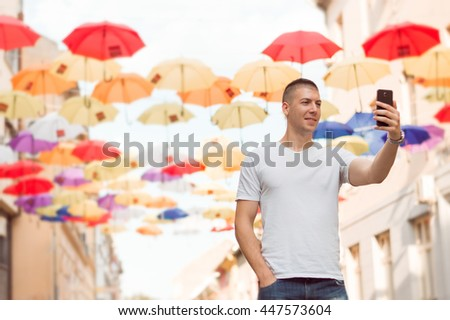 Selfie. Young smiling caucasian man taking selfie while walking on street with colourful umbrellas. - stock photo