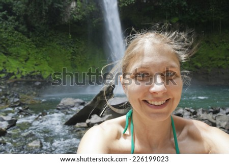 Selfy of a young woman in front of a waterfall - Catarata Rio Fortuna, La Fortuna, Alajuela province, Costa Rica