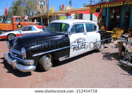 SELIGMAN, ARIZONA - AUGUST 16, 2014: Old Police car parked in front of Historic Seligman Sundries, on August 16, 2014 in Seligman, AZ. This town retains all the flavor of the old Route 66. - stock photo