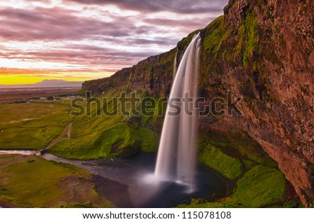 Seljalandsfoss is one of the most beautiful waterfalls on the Iceland. It is located on the South of the island. This photo is taken during the incredible sunset at approx. 1 AM. - stock photo