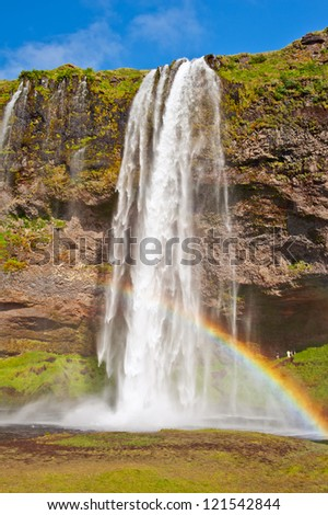 Seljalandsfoss is one of the most beautiful waterfalls on the Iceland. It is located on the South of the island. With a rainbow. - stock photo