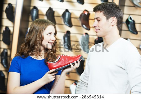 seller female assistant demonstrate shoes to young man during footwear shopping at shoe shop - stock photo